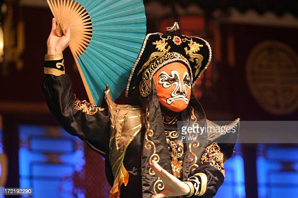 A Chinese opera actor performing with a mask on