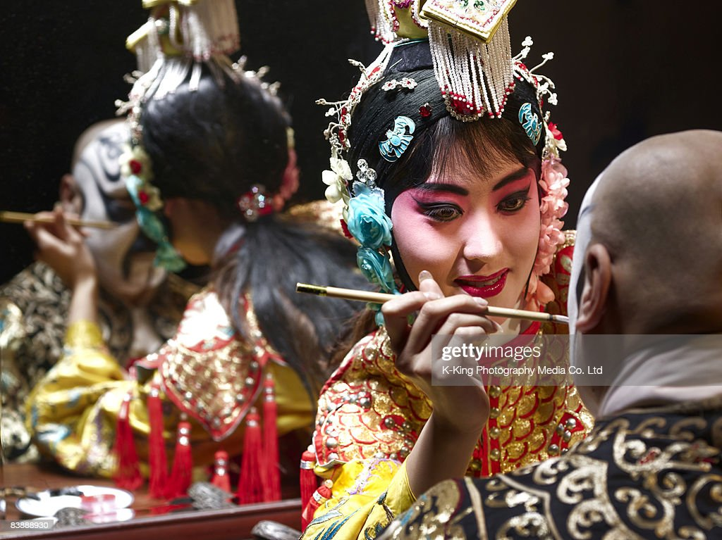 Chinese opera singer applying makeup to male : Stock Photo