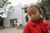 A Chinese orphan Lin Chuanxiu whose parents died of AIDS stares at the ground outside the elementary school of Gongmin Township on November 30 2005...