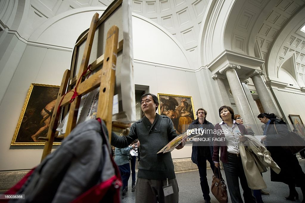 Chinese painter Guo Zhongzheng works on his painting, a copy of Titian's painting 'The emperor Charles V at Muchlberg' at the Prado Museum in Madrid on January 25, 2013. Chinese artists from the state academy and the China Academy of Art are due to make first-hand copies of some of the jewels of European oil painting and take them back to China to use for teaching. AFP PHOTO / DOMINIQUE FAGET