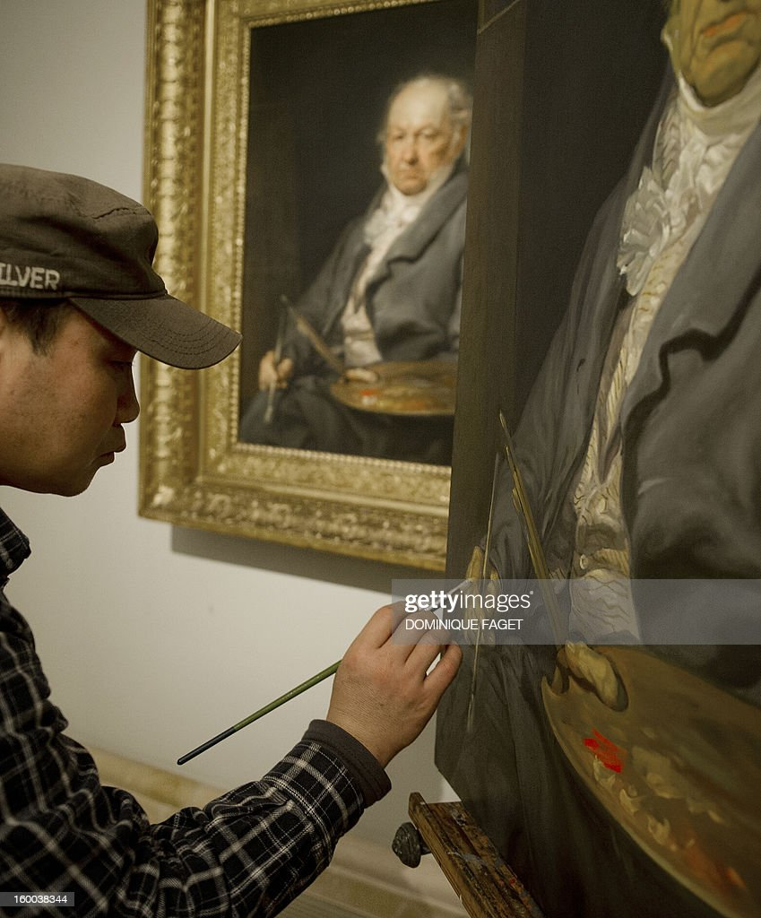Chinese painter Sun Wengong works on his painting, a copy of Vicente Lopez's painting 'El pintor Francisco de Goya' (Painter Francisco de Goya) at the Prado Museum in Madrid on January 25, 2013. Chinese artists from the state academy and the China Academy of Art are due to make first-hand copies of some of the jewels of European oil painting and take them back to China to use for teaching. AFP PHOTO / DOMINIQUE FAGET