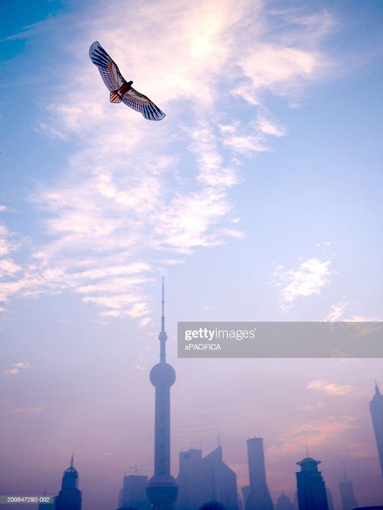 Chinese paper kite soaring above Pudong skyline, Shanghai, China : Stock Photo