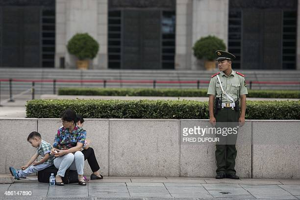 A Chinese paramilitary guard stands beside a woman with children in Tiananmen Square in Beijing on September 1 prior to a military parade on...