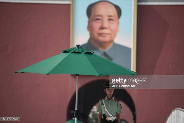 Chinese paramilitary guard stands in front of a portrait of late communist leader Mao Zedong at the Forbidden City in Beijing on July 31 on the eve...