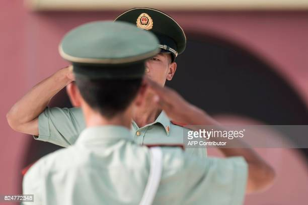 Chinese paramilitary guards salute in front of The Forbidden City in Beijing on July 31 on the eve of the 90th founding anniversary of the People's...