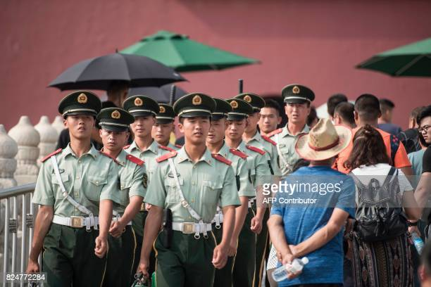 Chinese paramilitary guards walk in front of The Forbidden City in Beijing on July 31 on the eve of the 90th founding anniversary of the People's...
