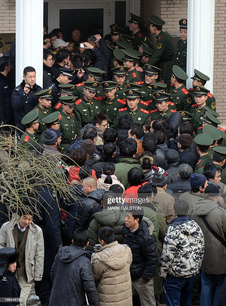 Chinese paramilitary police block access to the residence of a construction firm boss after a group of up to 50 migrant workers stormed past security at the Qijiayuan Diplomatic Compound to protest against what they claim is an unpaid new year bonus in Beijing on January 14, 2013. Labour unrest and disputes are common before the Chinese New Year when migrant workers are paid for their full years work in a lump sum before heading home to their famillies in outer provinces of the country. AFP PHOTO/Mark RALSTON