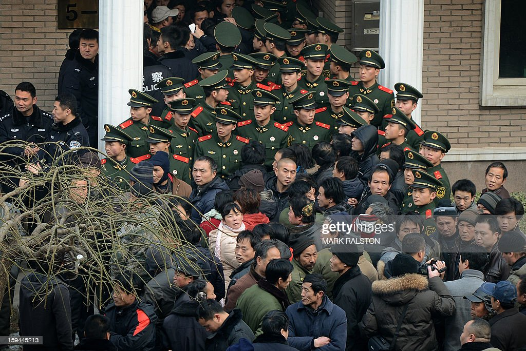 Chinese paramilitary police block access to the residence of a construction firm boss after a group of up to 50 migrant workers stormed past security at the Qijiayuan Diplomatic Compound to protest against what they claim is an unpaid new year bonus, in Beijing on January 14, 2013. Labour unrest and disputes are common before the Chinese New Year when migrant workers are paid for their full years work in a lump sum before heading home to their famillies in outer provinces of the country. AFP PHOTO/Mark RALSTON