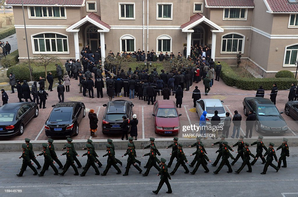 Chinese paramilitary police march past the residence of a construction firm boss after a group of up to 50 migrant workers stormed past security at the Qijiayuan Diplomatic Compound to protest against what they claim is an unpaid new year bonus in Beijing on January 14, 2013. Labour unrest and disputes are common before the Chinese New Year when migrant workers are paid for their full years work in a lump sum before heading home to their famillies in outer provinces of the country. AFP PHOTO/Mark RALSTON