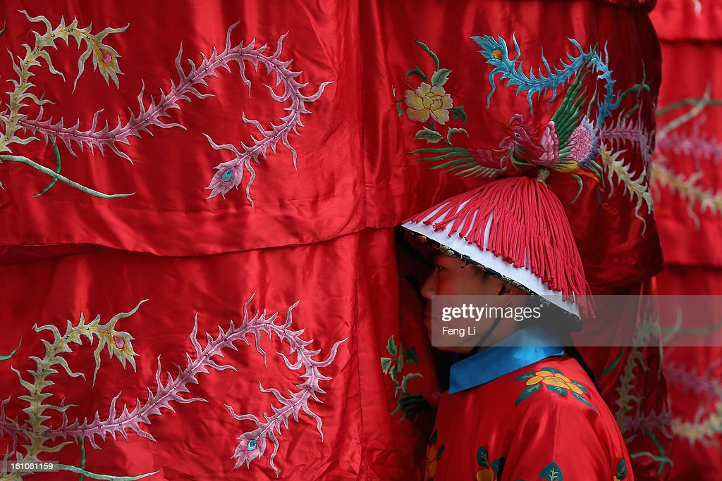 A Chinese paramilitary police officer dressed as a Qing Dynasty servant before a re-enactment of an ancient ceremony of Qing Dynasty emperors praying for good harvest and fortune during the opening ceremony of the Spring Festival Temple Fair at the Temple of Earth park on February 9, 2013 in Beijing, China. The Chinese Lunar New Year of Snake also known as the Spring Festival, which is based on the Lunisolar Chinese calendar, is celebrated from the first day of the first month of the lunar year and ends with Lantern Festival on the Fifteenth day.