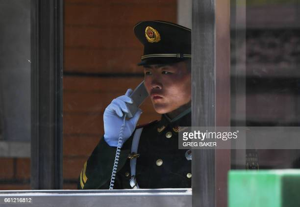 A Chinese paramilitary police officer makes a phone call outside the North Korean embassy in Beijing on March 31 2017 A flight from Malaysia believed...