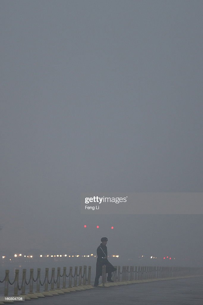 A Chinese paramilitary police officer passes through Changan Avenue during the flag-raising ceremony with severe pollution at Tiananmen Square on January 29, 2013 in Beijing, China. The 4th dense fog envelops Beijing with pollution at hazardous levels in January.