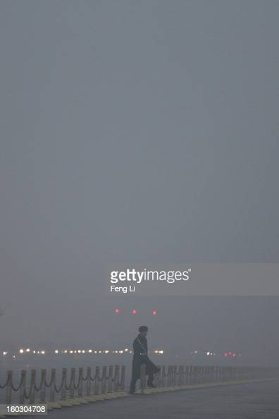 Chinese paramilitary police officer passes through Changan Avenue during the flagraising ceremony with severe pollution at Tiananmen Square on...