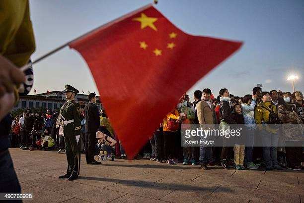A Chinese paramilitary police officer stands guard as crowds gather at the official flag raising ceremony at Tiananmen Square to mark the 66th...
