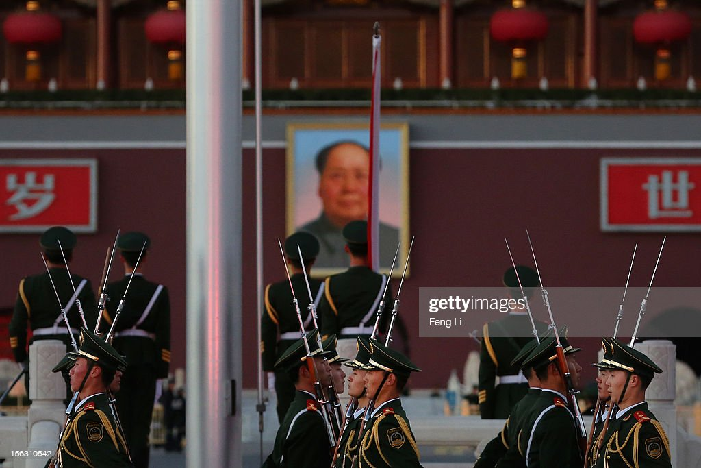 Chinese paramilitary police officers march during the flag-lowering ceremony in front of a giant portrait of the late chairman Mao Zedong at Beijing's Tiananmen Square on November 13, 2012 in Beijing, China. The 18th National Congress of the Communist Party of China (CPC) will close Wednesday morning after electing members and alternate members of a new CPC Central Committee and members of a new Central Commission for Discipline Inspection.