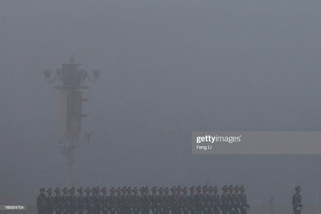 Chinese paramilitary police officers march during the flag-raising ceremony with severe pollution at Tiananmen Square on January 29, 2013 in Beijing, China. The 4th dense fog envelops Beijing with pollution at hazardous levels in January.