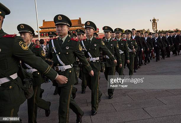 Chinese paramilitary police officers march following the official flag raising ceremony at Tiananmen Square to mark the 66th National Day on October...