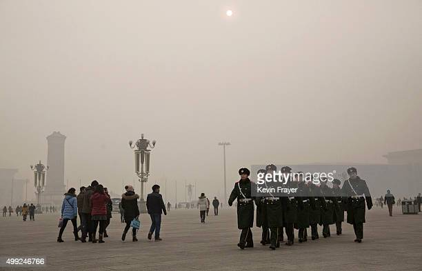 Chinese Paramilitary Police officers march through Tiananmen Square as the sun is seen on a day of heavy pollution on November 30 2015 in Beijing...