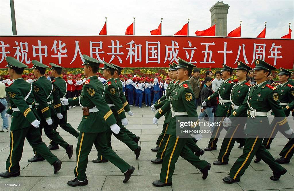 Chinese paramilitary police officers patrol near a billboard of China 58th National Day celebration displayed at the Tiananmen Square in Beijing, 29 September 2007. The Chinese capital is gearing up for its 58th National Day celebration 01 October and the 17th Communist Party Congress in mid-October, which could lead to personnel changes in the top echelons of power and will set China's political and economic course for the next five years. AFP PHOTO/TEH ENG KOON