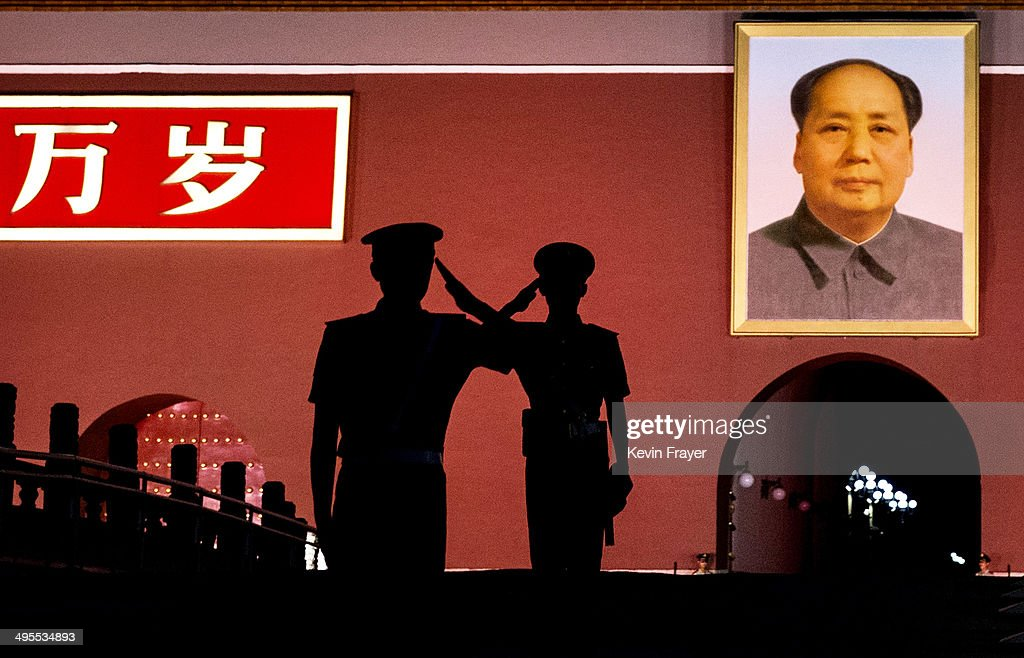 Chinese Paramilitary police officers salut each other as they stand guard below a portrait of the late leader Mao Zedong in Tiananmen Square on June 4, 2014 in Beijing, China. Twenty-five years ago on June 4, 1989 Chinese troops cracked down on pro-democracy protesters and in the clashes that followed scores were killed and injured.