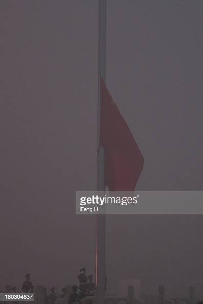 Chinese paramilitary police officers salute during the flagraising ceremony with severe pollution at Tiananmen Square on January 29 2013 in Beijing...