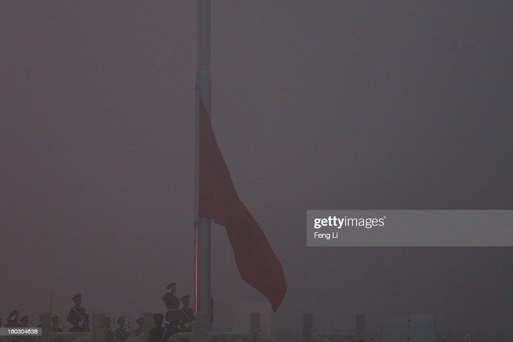 Chinese paramilitary police officers salute during the flag-raising ceremony with severe pollution at Tiananmen Square on January 29, 2013 in Beijing, China. The 4th dense fog envelops Beijing with pollution at hazardous levels in January.