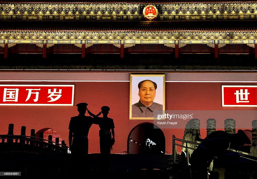 Chinese Paramilitary police officers salute each other as they stand guard below a portrait of the late leader Mao Zedong in Tiananmen Square on June 4, 2014 in Beijing, China. Twenty-five years ago on June 4, 1989 Chinese troops cracked down on pro-democracy protesters and in the clashes that followed scores were killed and injured.