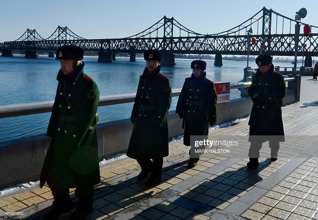 Chinese para-military police patrol beside the Sino-Korean Friendship bridge that links the North Korean town of Sinuiju with the Chinese town of Dandong on February 10, 2013. US Secretary of State John Kerry warned that North Korea's expected nuclear tests only increase the risk of conflict and would do nothing to help the country's stricken people. The country has vowed to carry out a third nuclear test soon, and concerns have been raised over the type of fissile material used in the device. AFP PHOTO/Mark RALSTON
