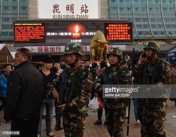Chinese paramilitary police patrol outside the scene of the attack at the main train station in Kunming Yunnan Province on March 3 2014 Knifewielding...