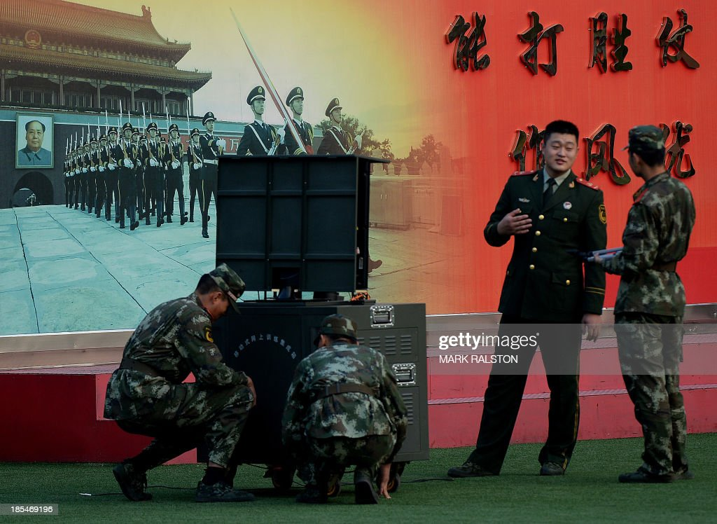Chinese paramilitary police set up a mobile internet data receiver at their barracks beside the Forbidden City in central Beijing on October 21, 2013. China's annual military spending has grown on average by double-digit rates over the past 20 years or so, according to Taiwan's 2013 National Defence Report. AFP PHOTO/Mark RALSTON