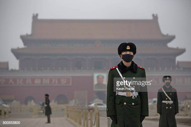 Chinese Paramilitary police wear masks to protect against pollution a rare occurence as they stand guard during smog in Tiananmen Square on December...