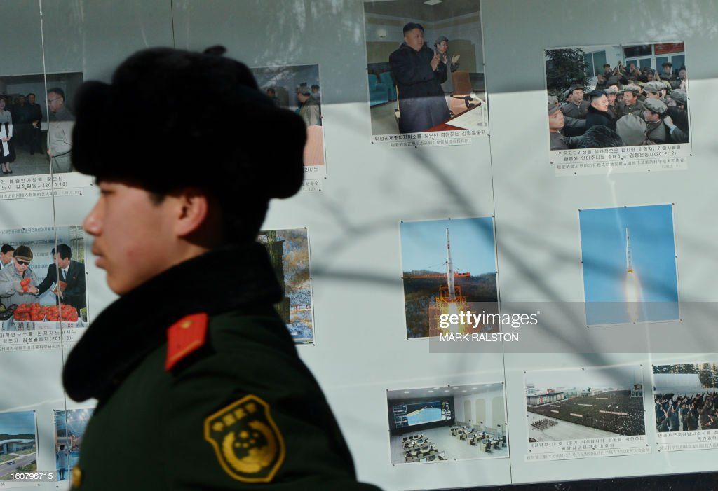 A Chinese para-military policeman marches past photos of North Korea's recent rocket launch on display outside the North Korean embassy in Beijing on February 6, 2013. China should exact a 'heavy price' from North Korea if it carries out a planned nuclear test, state-run media said on February 6, in an unusually strongly-worded call for action by Pyongyang's closest ally. AFP PHOTO / Mark RALSTON