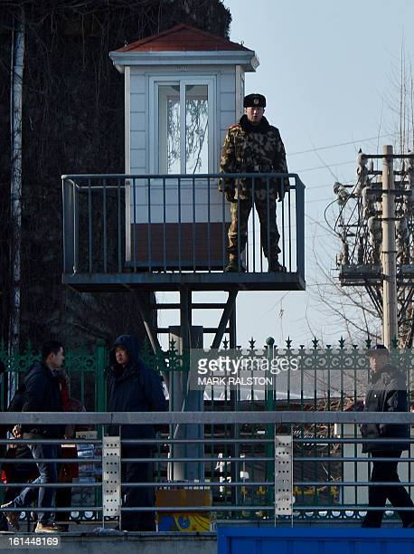 A Chinese paramilitary policeman stands guard on the banks of the Yalu River as he watches traffic from the North Korean town of Sinuiju on February...