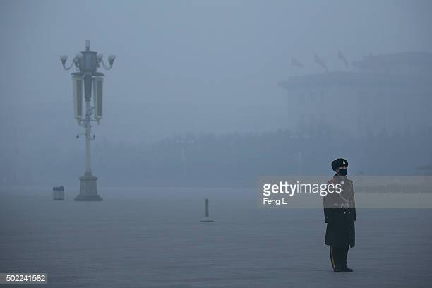 Chinese paramilitary policeman wears mask to protect against pollution as he guards during heavy pollution day in Tiananmen Square on December 22...