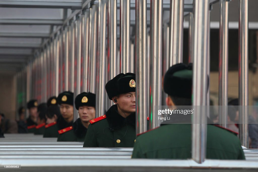 Chinese paramilitary policemen guard at the entrance of the check-in kiosks for real-name tickets at Beijing West Railway Station on January 8, 2012 in Beijing, China. China's annual Spring Festival travel rush begins on Sunday, and authorities estimate 3.158 billion passenger journeys will be made for the Chinese lunar new year during the 40-day travel period.