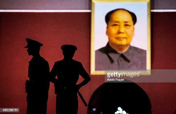 Chinese Paramilitary security force officers stand under a portrait of the late Mao Zedong outside the Forbidden City at Tiananmen Square on June 2...