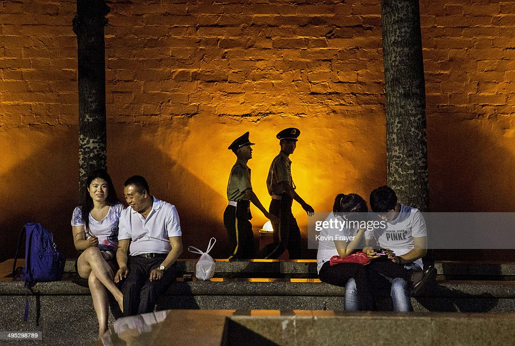 Chinese Paramilitary security force officers walk passed couples as they sit near Tiananmen Square on June 2, 2014 in Beijing, China. Twenty-five years ago on June 4, 1989, Chinese troops cracked-down on pro-democracy protesters leaving scores dead and injured.