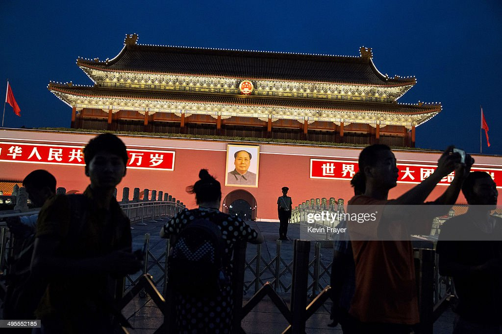 A Chinese Paramilitary soldier stands guard under a portrait of the late leader Mao Zedong as tourists pass by in front of the Forbidden City at Tiananmen Square on June 4, 2014 in Beijing, China. Twenty-five years ago on June 4, 1989 Chinese troops cracked down on pro-democracy protesters and in the clashes that followed scores were killed and injured.
