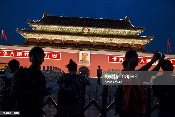 Chinese Paramilitary soldier stands guard under a portrait of the late leader Mao Zedong as tourists pass by in front of the Forbidden City at...