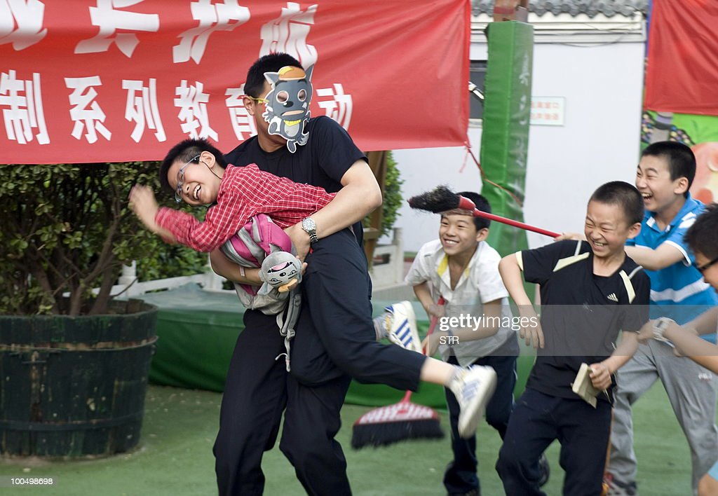 A Chinese parent shows school children an attack, during a demonstration at an elementary school in Beijing on May 24, 2010. Beijing police are recruiting parents to join patrols of school grounds as cities nationwide beef up security following a spate of attacks on children. CHINA