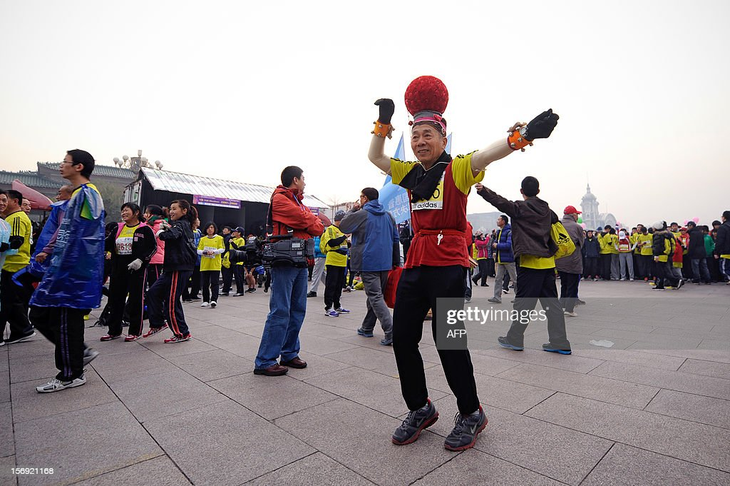 A Chinese participant dances before the start of the Beijing Marathon in the Chinese capital on November 25, 2012. A total of 30,000 runners took part in the race.