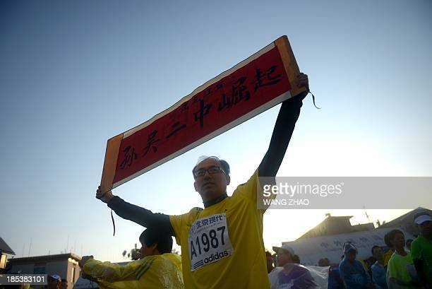 A Chinese participant holds up a slogan of inspiration as he prepares for the race before the start of the Beijing Marathon in the Chinese capital on...