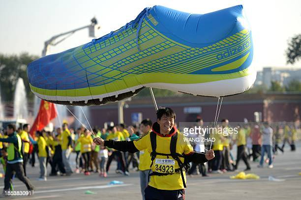 A Chinese participant holds up an inflatable model of a shoe at the start of the Beijing Marathon in the Chinese capital on October 202013 A total of...