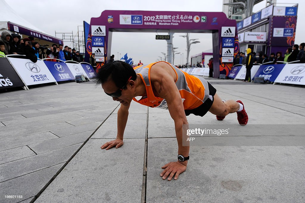 A Chinese participant rests after completing the Beijing Marathon in the Chinese capital on November 25, 2012. A total of 30,000 runners took part in the race.
