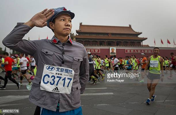 Chinese participant salutes as he wears an old Communist Party style uniform in front of Tiananmen Gate while competing in the 2015 Beijing Marathon...