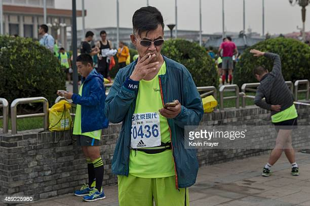 Chinese participant smokes a cigarette before competing in the 2015 Beijing Marathon on September 20 2015 in Beijing China Thousands of runners from...