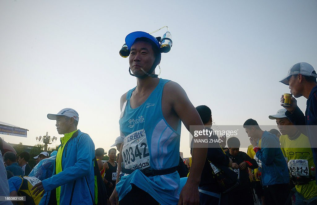 A Chinese participant wears drinking head gear equipment as he prepares for the race before the start of the Beijing Marathon, in the Chinese capital on October 20,2013. A total of 30,000 runners took part in the race.