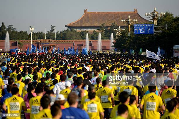 Chinese participants run past Tiananmen square and the Forbidden City at the start of the Beijing Marathon in the Chinese capital on October 20 2013...