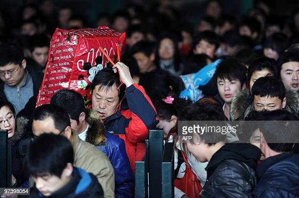 Chinese passengers rush to board trains at a railway station in Beijing on February 10 2010 Millions of Chinese crowded into airports train terminals...