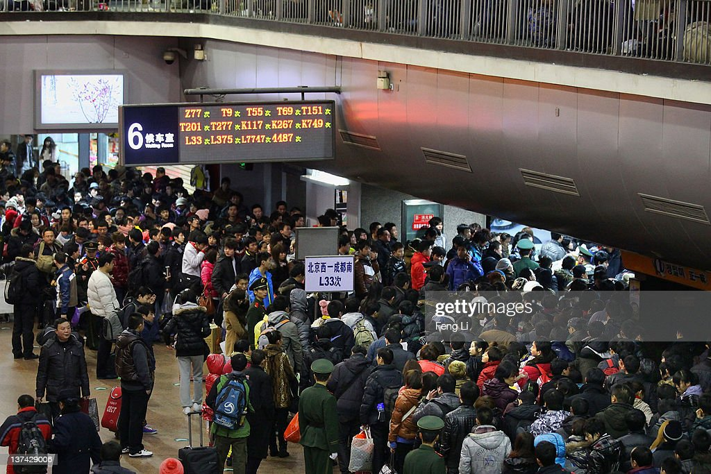 Chinese passengers wait to board a train to go their hometown at Beijing West Railway Station during the Spring Festival season on January 20, 2012 in Beijing, China. Chinese people are preparing for the lunar new year of Dragon, which will fall on January 23, 2012. New year celebrations are also refered to as The Spring Festival.